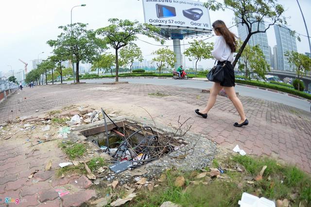 """Khu vực vỉa hè trên đường Trần Duy Hưng – Phạm Hùng (quận Cầu Giấy) chỉ chưa đầy 100 m xuất hiện liên tiếp 5-7 hố cáp điện ngầm và đường ống dẫn nước toang hoác gây nguy hiểm cho người đi bộ.    Đoạn vỉa hè này có một trạm xe buýt, siêu thị và hầm bộ hành nên người qua lại khá đông đúc.      Anh Nguyễn Văn Toản (Hưng Yên) chạy xe ôm ở khu vực này cho biết, mấy nắp cống được nhấc lên hôm trước thì hôm sau có đội khác đến làm nhưng không thấy ai có ý định đặt lại vị trí cũ.      Dây cáp điện trồi lên khỏi hố ngầm.      Nắp cống sứt mẻ, không còn nguyên vẹn, xuất hiện những đoạn sắt thép trồi lên mặt đất.      Thu Hương (sinh viên Đại học Lao động – Xã hội) cho biết em hàng ngày thường xuyên đi lại qua khu vực này. May mắn em chưa bị dính phải """"bẫy"""" từ các miệng cống mấp nắp nhưng đã từng nhìn thấy một số trường hợp bị vấp ngã.      Những chiếc hố như thế này trên phố Trung Kính (quận Cầu Giấy) còn kiêm luôn một chiếc thùng chứa rác.      Dây cáp điện một nơi, hố một nẻo khu vực Mỹ Đình (quận Nam Từ Liêm).      Nắp cống tạo khoảng hở dài 1 m, rộng 30 cm trên đường Nguyễn Xiển (quận Thanh Xuân).      Nắp cống dở dang tại đường Nguyễn Xiển.      Vỉa hè trên đường Kim Mã (quận Ba Đình) cũng xuất hiện """"hố tử thần"""" có một số vật dụng đặt quanh miệng nhằm """"cảnh báo"""" người đi bộ.      Đoạn đầu đường Khương Đình (quận Thanh Xuân), một số miệng cống được đặt tạm bợ bằng các tấm ván gỗ."""