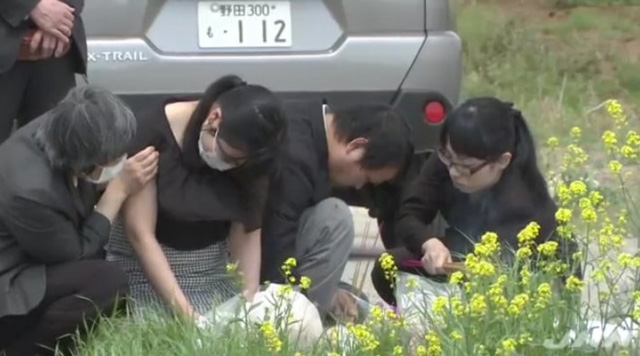 Bố mẹ của bé Linh thắp nhang tại nơi thi thể con gái được phát hiện. Ảnh chụp màn hình.