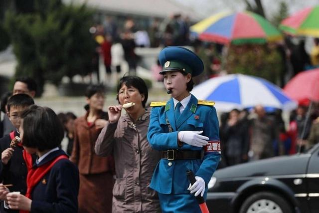 Một cảnh sát giao thông đang chỉ dẫn người dân và các phương tiện trên đường hôm 16/4. Phía sau cô là một phụ nữ vừa đi vừa ăn kem.