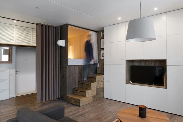 Căn hộ có diện tích sàn 35 m2, được thiết kế bởi Bazi Studio.    Một góc căn hộ được thiết kế nâng lên thành giường ngủ.      Chiếc hộp ngủ đủ chỗ cho hai người, tuy nhiên chủ nhân chỉ có thể ngồi, không đứng được trong hộp.      Không gian sinh hoạt chính được ngăn cách với khu vực cửa ra vào bằng một rèm lớn cùng màu gỗ.      Bên dưới giường ngủ là tủ đồ dạng ngăn kéo, gồm ba ngăn lớn giúp chủ nhân có thêm không gian chứa đồ. Bậc thang lên giường ngủ cũng là những ngăn kéo ẩn để chứa đồ.      Ngay cả những góc nhỏ nhất trong căn hộ cũng được tận dụng để không lãng phí không gian.      Bếp ăn với nội thất mang tông trắng. Màu trắng giúp không gian có cảm giác rộng hơn thực tế. Tuy nhiên, kiến trúc sư vẫn khéo léo sử dụng gạch hoa để tạo điểm nhấn cho căn bếp nhằm tách biệt không gian.      Phòng tắm rộng rãi, có bồn tắm.      Mặt bằng căn hộ 35 m2. Theo kiến trúc sư, khi cần thiết sofa có thể được kéo áp tường để mở rộng căn bếp, phục vụ mở một bữa tiệc cho 10 người một cách thoải mái.