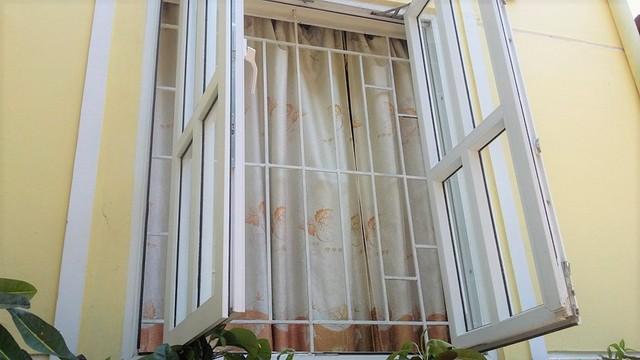 Hệ thống khung cửa khi bé Quỳnh Anh 2 tuổi rưỡi vượt qua và rơi xuống đất từ tầng 2. Sau sự việc, các khung cửa này đã được hàn thêm các thanh chắn ngang, với nhiều ô vuông nhỏ . Ảnh: Thanh Hùng.