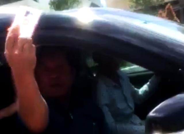 Người đàn ông ngồi trong xe còn giơ thẻ ngành ra để dọa CSGT - Ảnh chụp từ clip