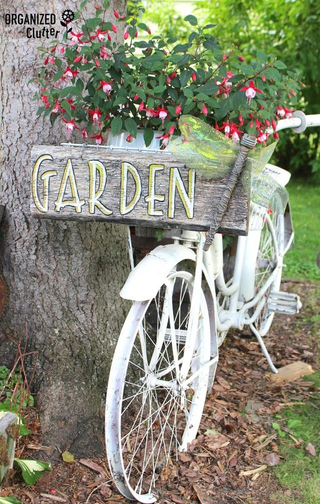 1. Tận dụng chiếc xe đạp cũ nhà mình để gắn biển cho khu vườn sau nhà của bạn chắc chắn là một ý tưởng hay ho. Thêm một chậu hoa được đặt trong giỏ xe là hoàn hảo rồi.