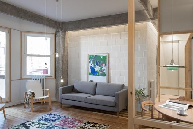 Căn hộ có diện tích sàn 100 m2. Tông màu chính của thiết kế là trắng, xám bê tông và nâu nhạt của gỗ.