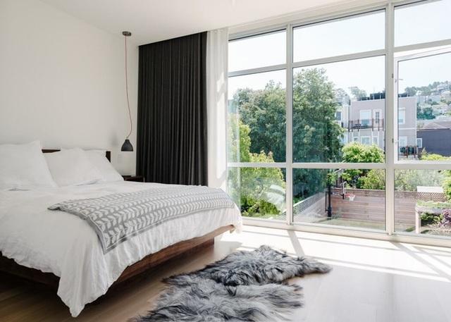 1. Với tông nội thất, ga gối màu trắng và bức tường kính rộng mở ra hướng nhìn nhiều cây xanh, phòng ngủ này không cần nhiều đồ đã vô cùng hấp dẫn. Dĩ nhiên để căn phòng thêm đẹp, bạn cần sắp xếp đồ dùng dọn dàng và hạn chế đồ không cần thiết nữa.