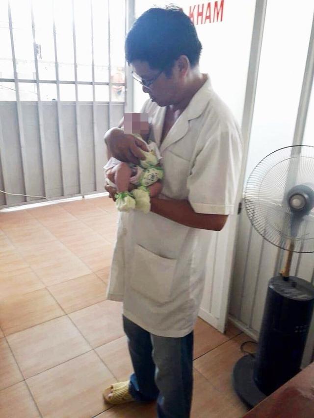 Bệnh nhi được BS Cao Văn Tuân ôm trên tay sau khi cấp cứu.