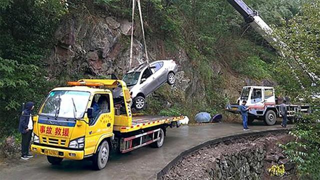 Chiếc xe hơi có thi thể người chồng bên trong được xe cứu hộ kéo lên.