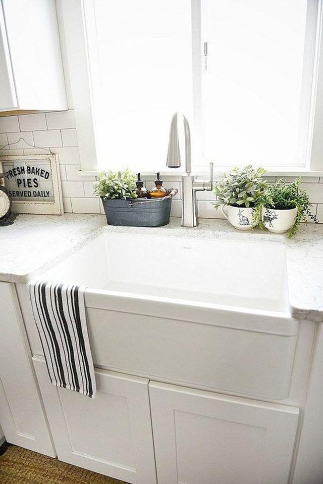 Mọi người hay có thói quen để những chai xà phòng, bọt biển rửa bát ngay trên thành của vòi nước. Về thẩm mĩ thì trông như thế sẽ không được đẹp và vệ sinh. Một gợi ý nhỏ cho bạn là bạn nên sử dụng một chậu cây xanh hai ngăn, một ngăn là cây cảnh trang trí, một ngăn rỗng có thành cao hơn để bạn để chai xà phòng và bọt biển. Trông nó sẽ gọn gàng và sạch sẽ hơn nhiều.