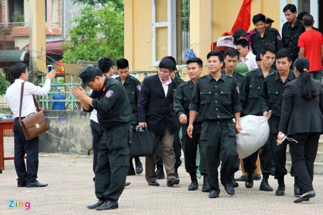 Thượng tá Phạm Văn Trung, Trung đoàn phó Trung đoàn Cảnh sát cơ động vào đón cán bộ, chiến sĩ. Anh chắp tay cảm ơn bà con thôn Hoành trong khi bước ra cổng. Ảnh: Zing.vn.