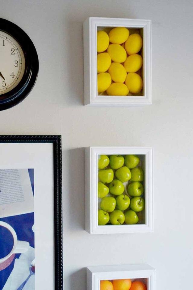 Tường bếp nổi bật với những tác phẩm nghệ thuật và những loại hoa quả giả.
