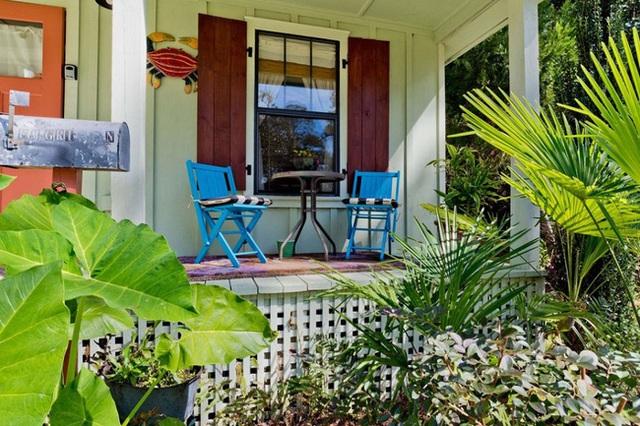 Hai bộ bàn ghế bên ngoài hiên được sơn màu hồng và xanh dương bắt mắt phù hợp với thời tiết nhiệt đới ở phía Nam.
