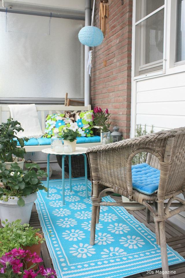 2. Miếng thảm trải sàn màu xanh có một ảnh hưởng hiện đại, mới mẻ trên một ban công có nhiều yếu tố thiên nhiên, chẳng hạn như việc lựa chọn sắp xếp các cây xanh. Màu sắc tràn đầy năng lượng của tấm thảm và đệm ghế ngồi tạo ra sự tương phản mạnh mẽ đối với bức tường gạch thô.