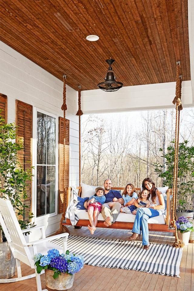 Hiên nhà với khoảng diện tích khá rộng, là nơi tuyệt vời để mọi người thiết kế ghế xích đu cỡ lớn. Thêm tấm thảm sọc xanh trắng yên bình cho những giờ thư giãn, trò chuyện, ngắm cảnh xung quanh thêm ý nghĩa.
