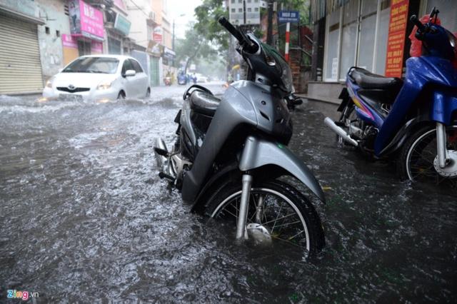 Xe máy để trên vỉa hè cũng bị ngập hơn nửa bánh. Nước đen kịt bốc mùi hôi thối.
