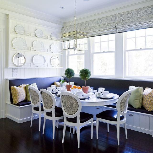 Ghế banquette màu trắng phủ đen tạo không gian ăn tối đơn giản mà trang trọng.