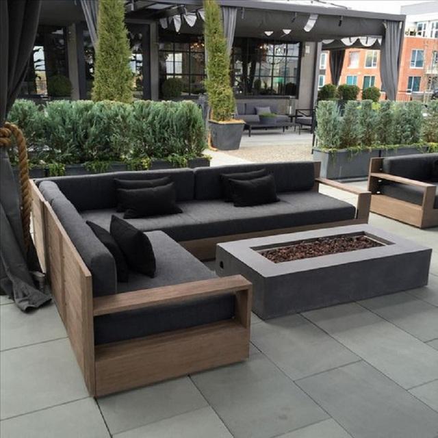 2. Còn đây lại là một bộ ghế sofa nghỉ dưỡng mới đặt trên một khung gỗ có chữ L và ghế có màu xám, gối ôm lại đen sì như than.