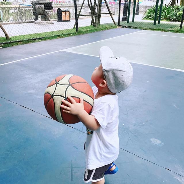 Cậu nhóc sắp tròn tuổi rưỡi ôm trái bóng ngước nhìn lên cột gôn.