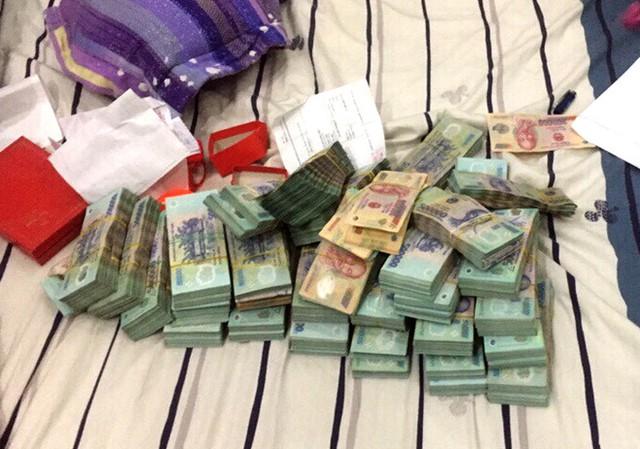 Cảnh sát thu giữ hơn 5 tỷ đồng và nhiều công cụ hỗ trợ đánh bạc. Ảnh: Thái Linh.