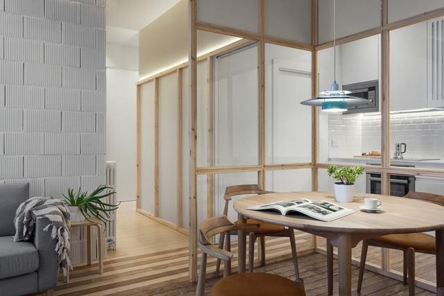 Phòng khách liền với phòng bếp, được chia tách không gian bằng khu vực bàn ăn quây kính độc đáo. Căn hộ kết hợp hài hòa những chi tiết bê tông thô cùng nội thất gỗ.