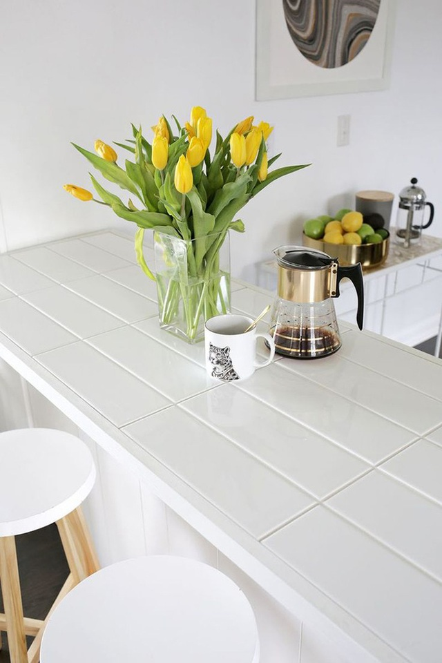 Đảo bếp dài với gạch và lớp xi măng màu trắng.