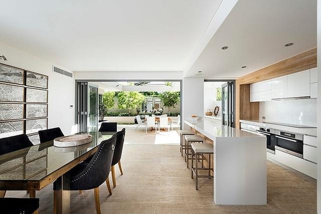 12. Bếp màu trắng tối giản với những món đồ gỗ màu ấm và không gian phòng ăn với những chiếc ghế màu đen tạo sự đối nghịch rõ nét.