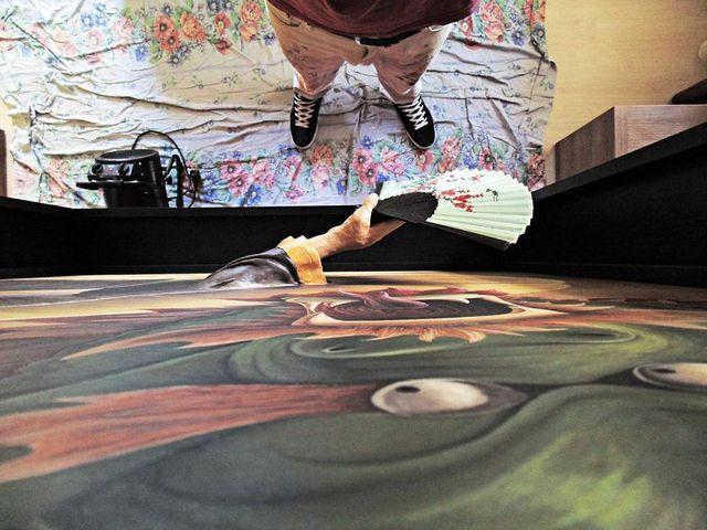 Một bức vẽ khắc hoạ lại một câu truyện trông vô cùng sống động với phần cánh tay cầm quạt được vẽ bằng nghệ thuật 3D như thật.