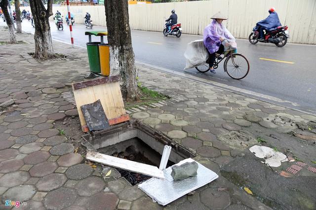 """Vỉa hè trên đường Kim Mã (quận Ba Đình) cũng xuất hiện """"hố tử thần"""" có một số vật dụng đặt quanh miệng nhằm """"cảnh báo"""" người đi bộ."""