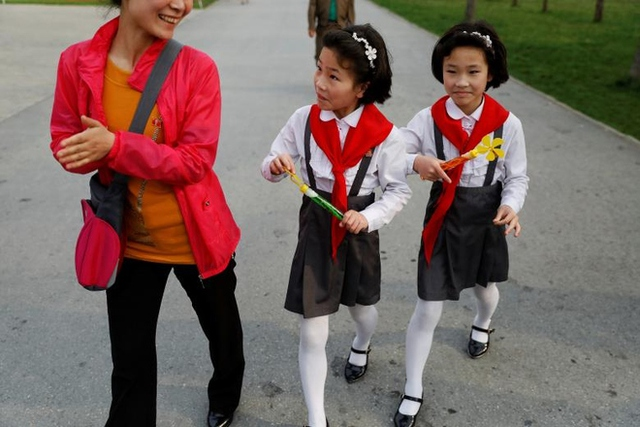 Hai bé gái sinh đôi đeo bờm hoa, thắt khăn quàng đỏ, tay cầm chong chóng xà phòng đi chơi cùng mẹ trong sở thú.