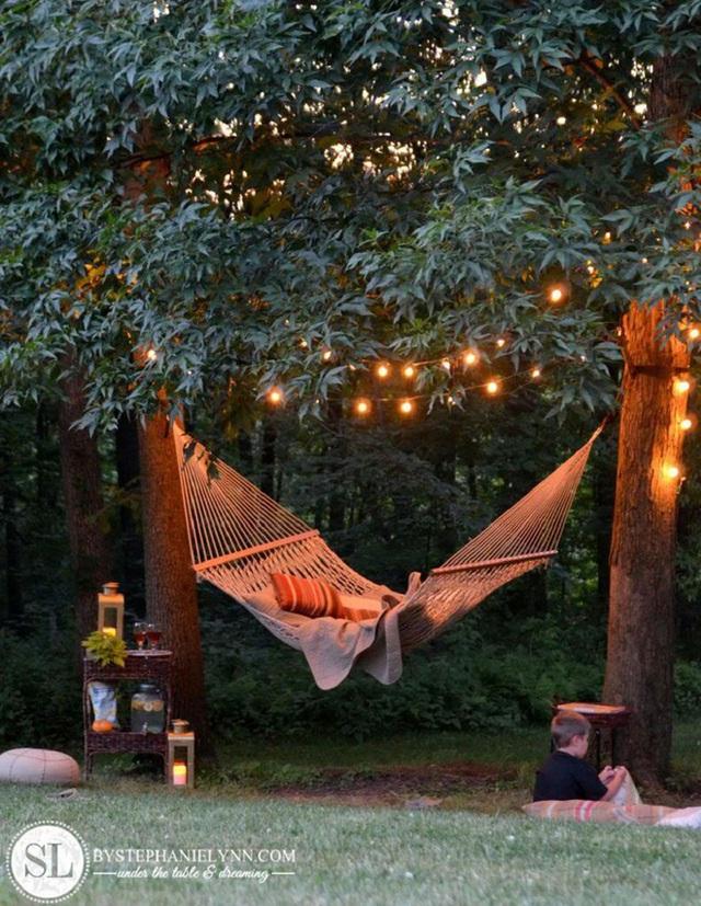 11. Một chiếc võng đu nhẹ nhàng bắc ngang qua hai cây cổ thụ, cùng ít dây lấp lánh sẽ biến khu vườn nhà bạn trở thành không gian thư giãn bậc nhất trong cả ngôi nhà.