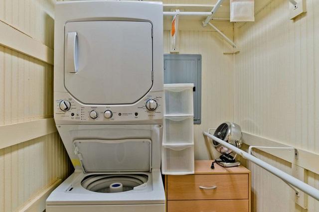 Một chiếc máy giặt cỡ lớn được đặt tại chân cầu thang để phục vụ nhu cầu sinh hoạt của cả gia đình.