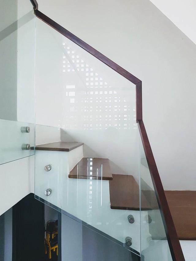 Cầu thang sử dụng kính thay vì song gỗ hoặc sắt, khiến không gian thoáng đãng hơn, tầm mắt không bị sạn.
