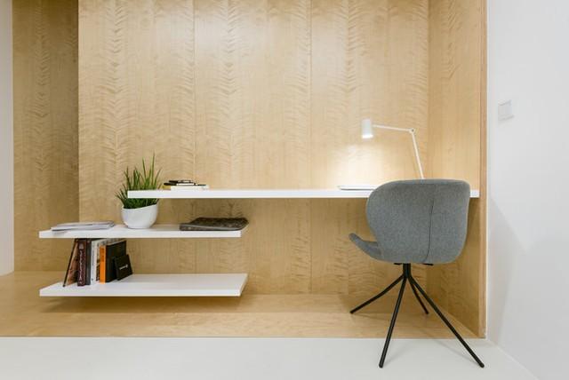 Phòng làm việc thiết kế sử dụng bàn làm việc cách điệu dạng kệ sách.