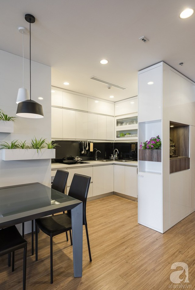 Góc ăn uống được bố trí ngay phía ngoài nơi nấu nướng. Khu vực chức năng cũng được chọn lựa nội thất với kiểu dáng đơn giản, màu sắc nổi bật trên nền không gian trắng dịu dàng.