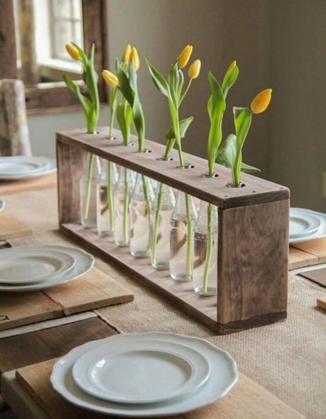 Tận dụng kệ gỗ vứt đi, bạn có thể khoan thành lỗ tương ứng miệng lọ thủy tinh để cắm hoa đầy nghệ thuật.