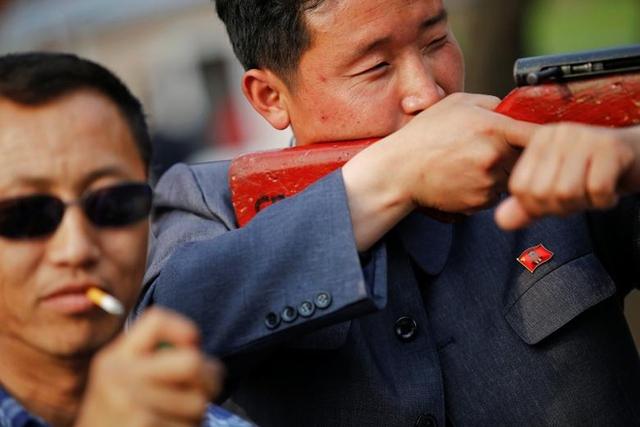Một người đàn ông đeo huy hiệu đảng in hình lãnh đạo Kim Nhật Thành bên ngực trái, chăm chú chơi trò bắn súng hơi trong sở thú.