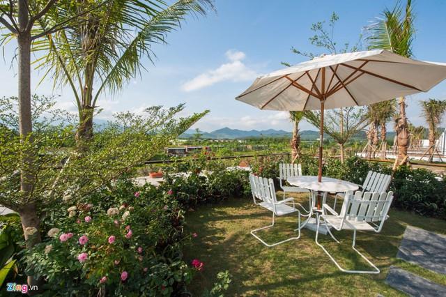 Vườn treo trồng hoa, thảm cỏ và bàn ghế thư giãn.