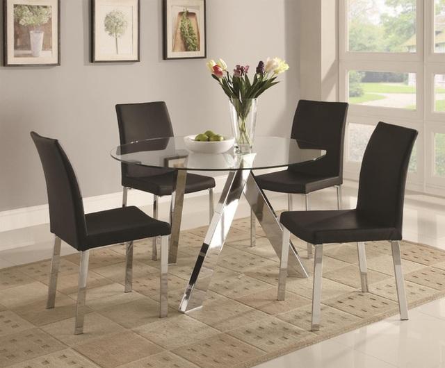 Bàn ăn bằng kính tròn với những chiếc ghế màu đen trang nhã mang đến một thông điệp rõ ràng về nội thất hiện đại. Do đó, một chiếc thảm trang trí cần làm chúng trở nên nổi bật hơn một cách tinh tế.