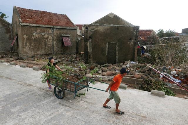Hai vợ chồng kéo xe chở đất qua dãy nhà tan hoang ở thôn Hải Nam.