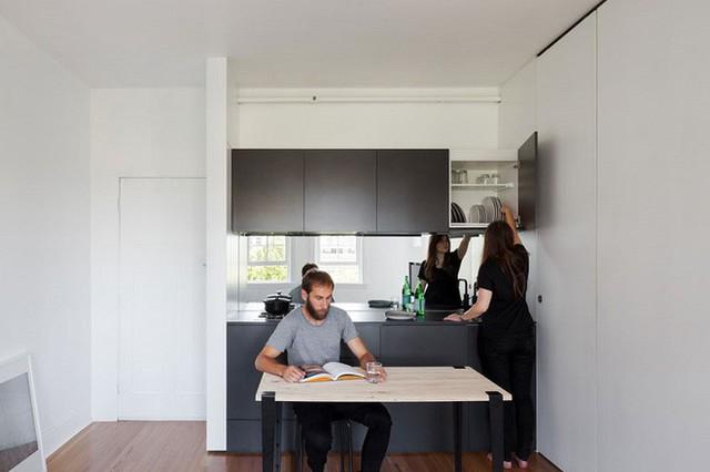 Đối diện với nhà khách và ngay gần lối cửa ra vào là bàn và bệ bếp. Với diện tích hẹp nên chủ nhân đã lựa chọn mẫu bàn nhỏ, với tủ và kệ đính tường gọn nhẹ đỡ mang cảm giác bộn bề, nhức mắt.