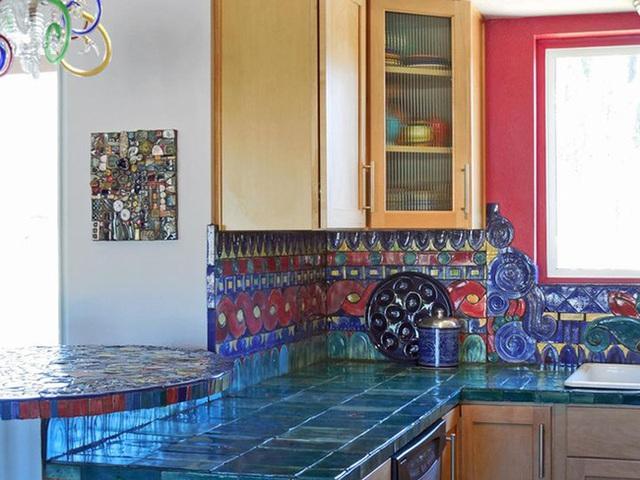 Gạch màu xanh mòng két đập trên đảo bếp và gạch màu đỏ và xanh dương cho tường bếp.