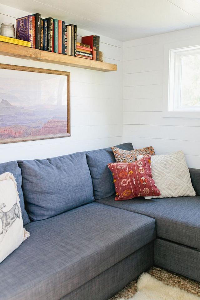 Phong cách Scandinavian chạy theo tới cả không gian nhà khách qua các mẫu hoa văn trên gối ôm.