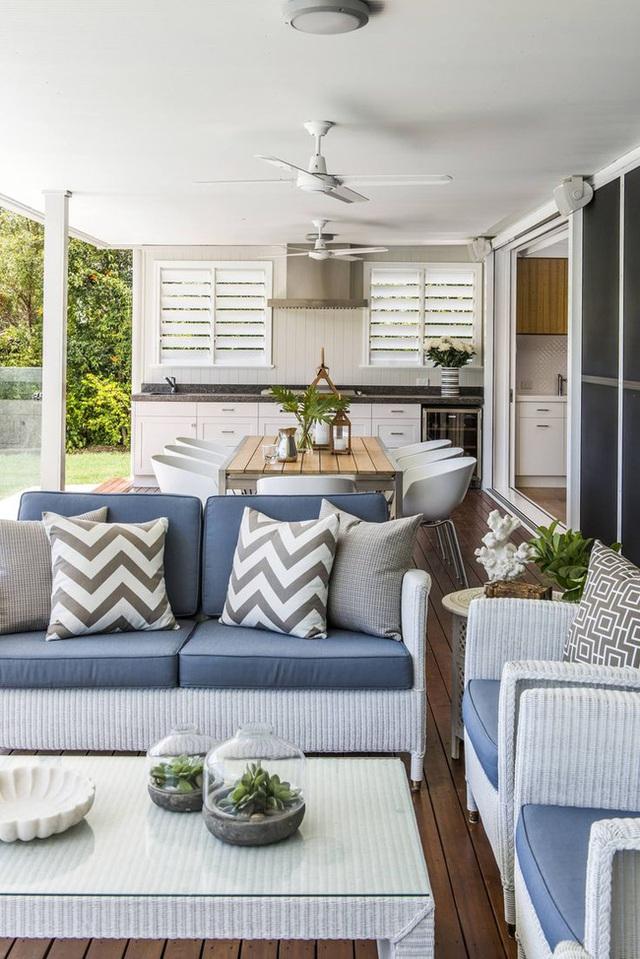 17. Phòng khách phong cách biển với nội thất bằng mây tre đan và phòng bếp với gam màu trắng cùng đảo bếp màu đen.