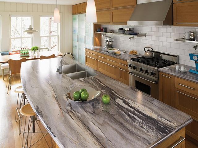 Đảo bếp bằng đá granit có gam màu lạnh tương phản với tủ gỗ màu ấm.