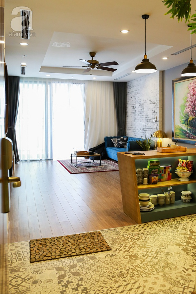 Không gian khách - bếp còn phân tách bởi chất liệu và màu sắc nền sàn. Cụ thể phòng khách ấm cúng với chất liệu gỗ, còn khu bếp là nền gạch hoa ấn tượng.