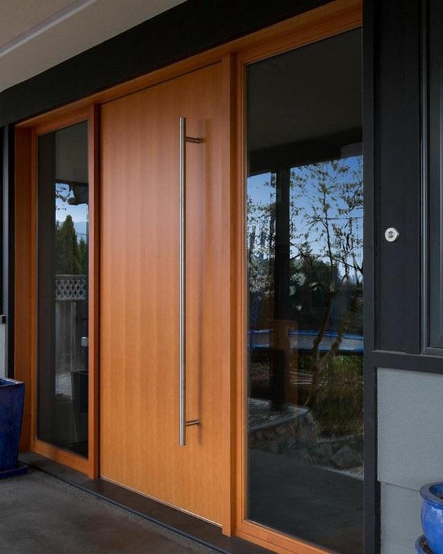 Không chỉ nổi bật trên nền đen bao quanh, thiết kế tay nắm cửa bằng thép không gỉ cỡ lớn cũng là điều tạo ra vẻ nổi bật của cánh cửa gỗ này.