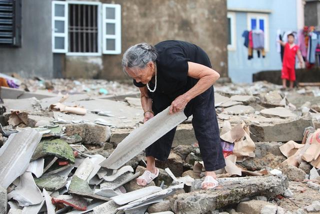Cụ bà cặm cụi dọn gạch, ngói vụn trên nền ngôi nhà đã bị bão đánh sập.