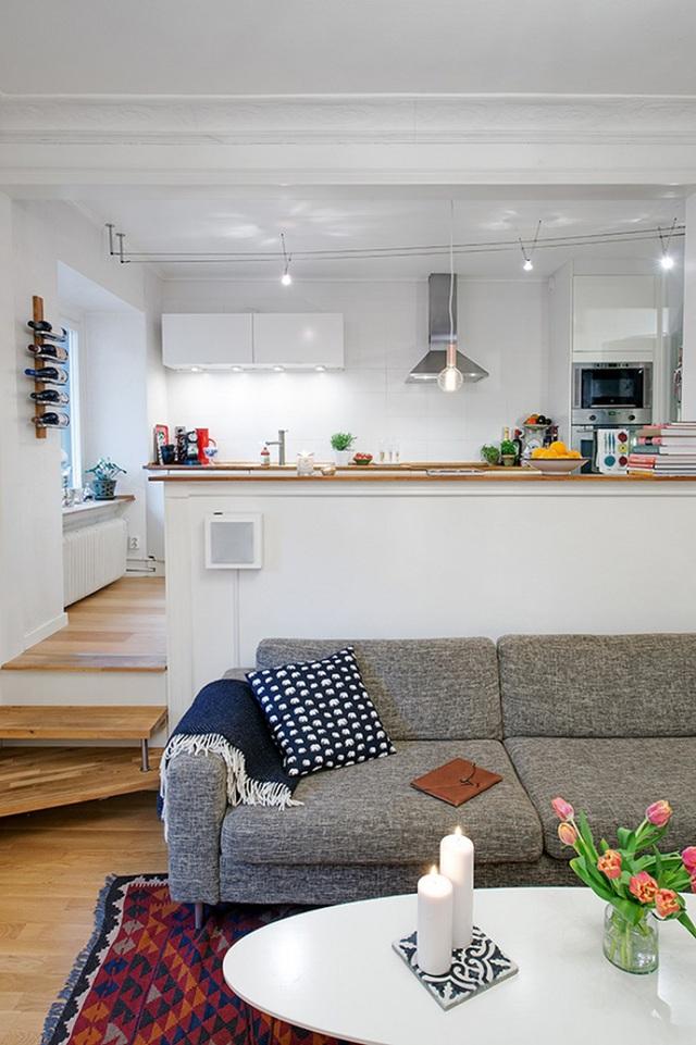 19. Bếp hiện đại màu trắng với rất nhiều đèn và phòng khách với ghế sofa nệm và gối tựa êm ái.