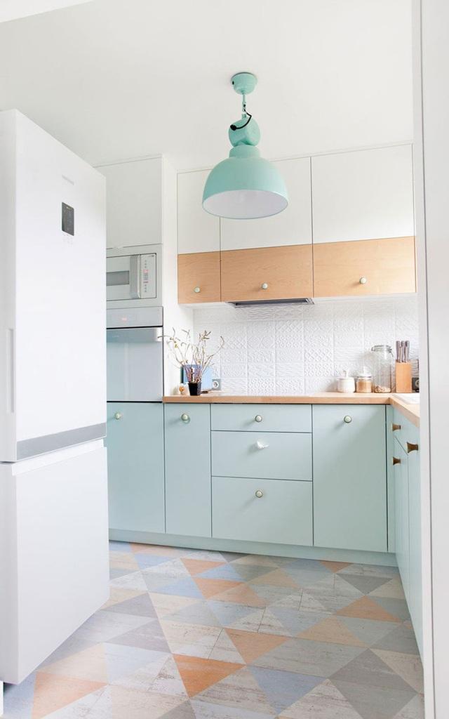 Tủ bếp màu xanh bạc hà dịu dàng kết hợp với sàn gỗ họa tiết hình học tone màu pastel tạo nên vẻ dịu dàng tinh tế cho góc bếp.