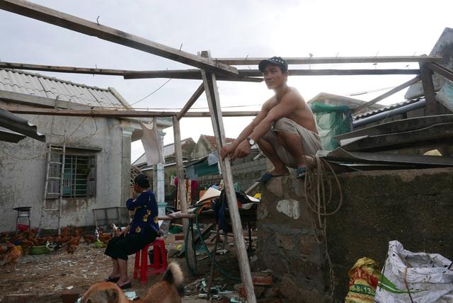 Người đàn ông ở thôn Hải Bắc ngôi buồn trên nền ngôi nhà đã bị bão phá tan tành. Nhà sập, đồ đạc hư hỏng, điện vẫn chưa có lại, cuộc sống trước mắt của nhiều người dân ở thôn Hải Bắc và Hải Nam khó khăn trăm bề.