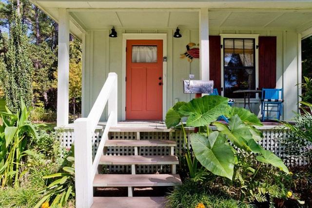 Cửa ra vào cũng được sơn màu da cam chói mắt, kết hợp với những cây rau cỏ bao quanh hành lang lối ra vào nhà tạo nên một không gian đồng quê tươi mát.